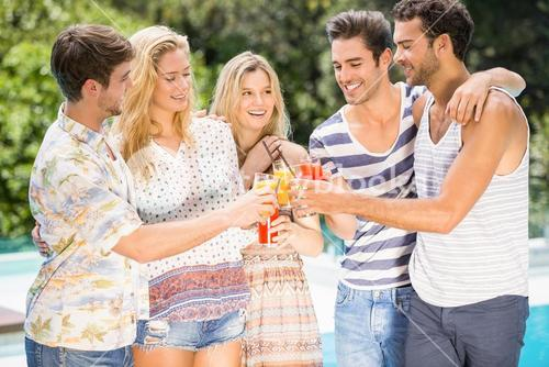 Group of friends toasting glasses of juice near pool