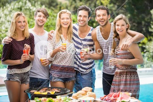 Portrait of friends having juice at outdoors barbecue party