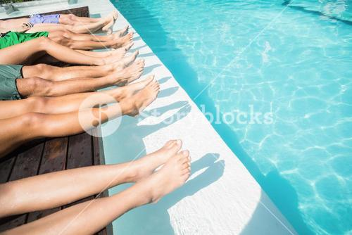 Feet of friends relaxing at poolside