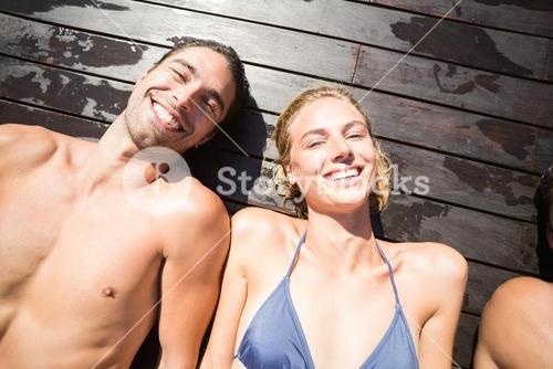 Smiling couple relaxing on wooden deck