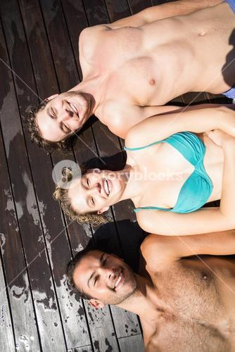 Smiling friends relaxing on wooden deck