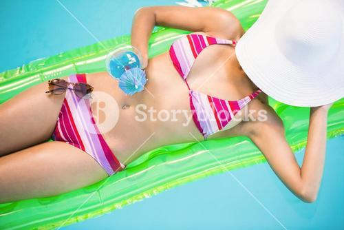 Beautiful woman relaxing on air bed in swimming poo