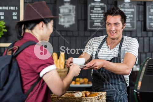 Waiter serving a coffee to a customer