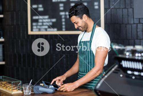 Handsome barista using cash register