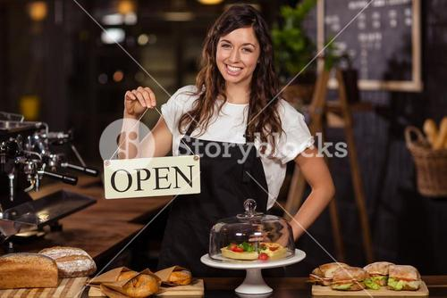 Pretty waitress holding a open sign