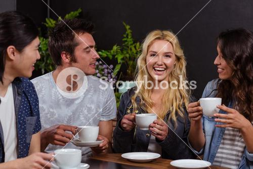 Smiling friends talking and enjoying coffee