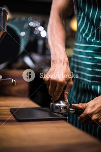 Waiter squeezing the coffee in the percolator