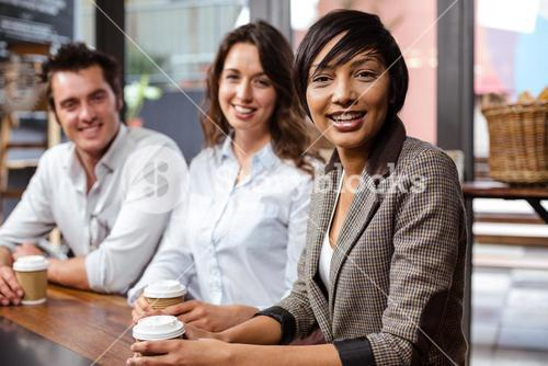 Smiling friends holding a cup of coffee