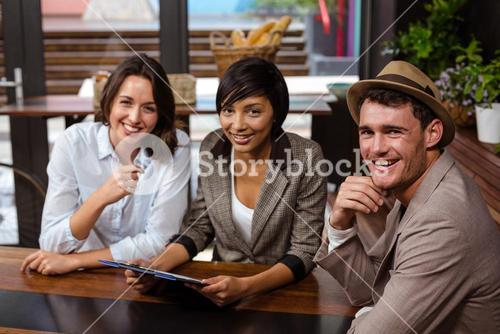 Smiling friends holding tablet