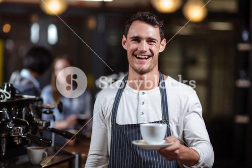Smiling barista holding cappuccino