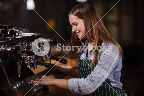 Smiling barista cleaning coffee machine