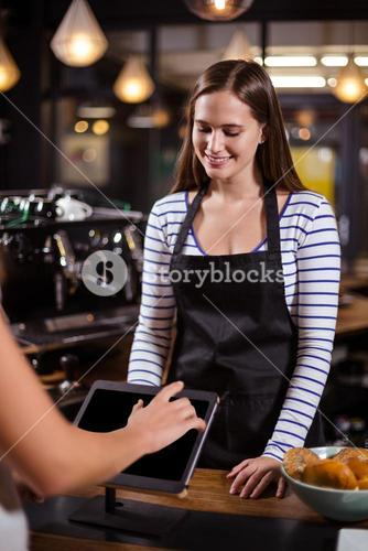 Smiling barista looking at tablet while woman is ordering