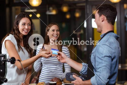 Smiling clients paying with card