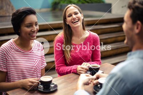 Happy friends having coffee together