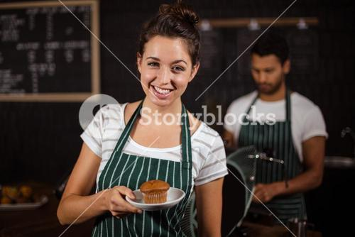 Smiling barista holding muffin