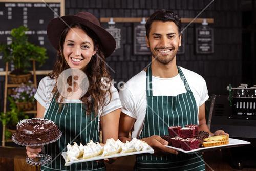 Smiling baristas holding trays with desserts