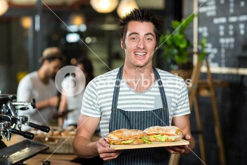 Smiling barista holding sandwiches