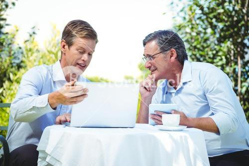 Two businessmen meeting in a restaurant using laptop