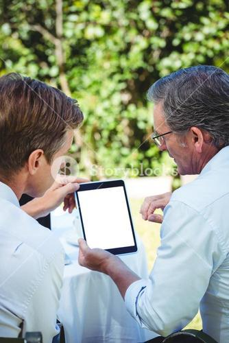 Two businessmen meeting in a restaurant using tablet