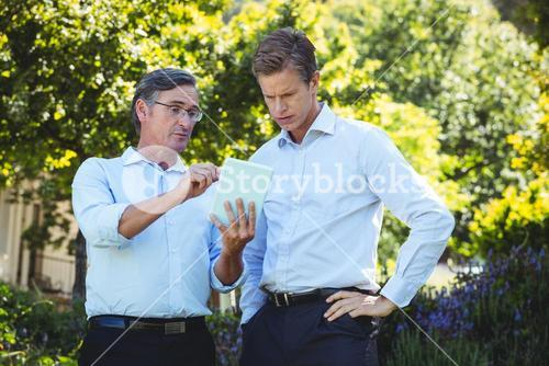 Two businessmen meeting using tablet
