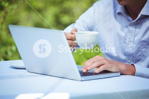Businessman using laptop with coffee