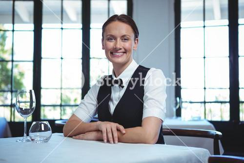 Waitress posing and sitting at the table