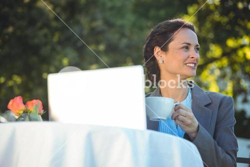 Businesswoman using laptop with coffee