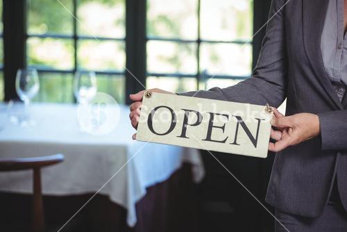 Businesswoman holding open sign
