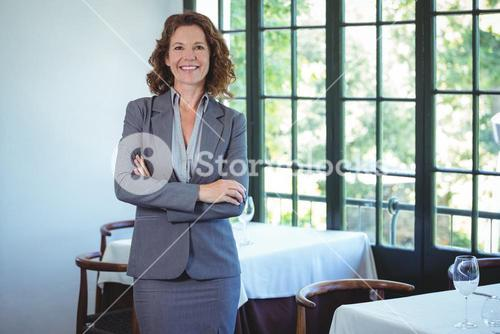Smiling businesswoman posing with crossed arms