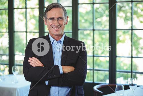Smiling businessman posing with crossed arms