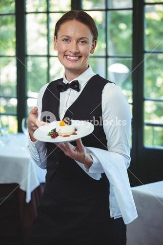 Smiling waitress holding a plate