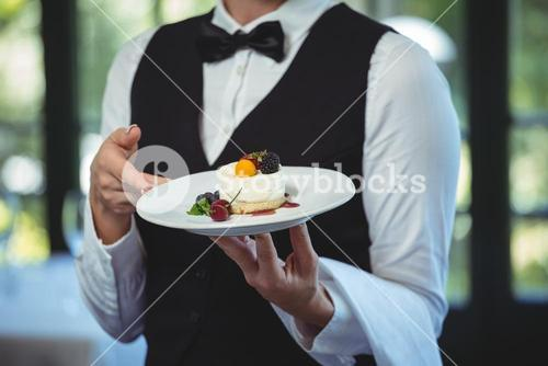 Waitress holding a plate with dessert