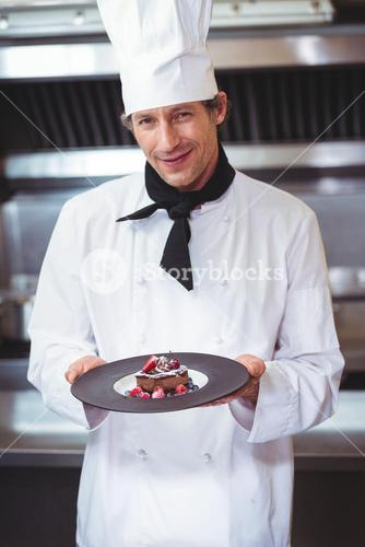 Chef holding a plate with a dessert