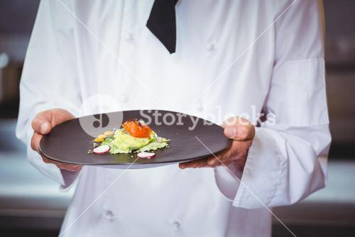 Chef holding and showing a dish