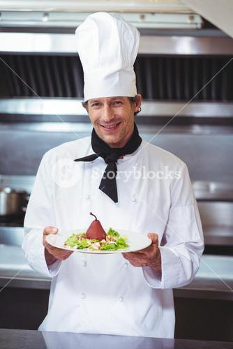 Chef holding a dish with salad