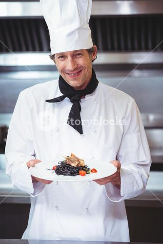 Chef holding a dish with spaghetti
