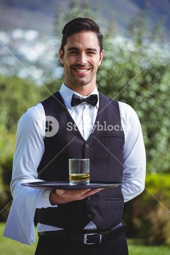 Handsome waiter holding a tray with glass of whiskey