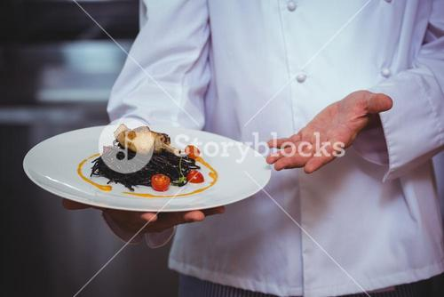 Proud chef holding a plate of squid ink spaghetti