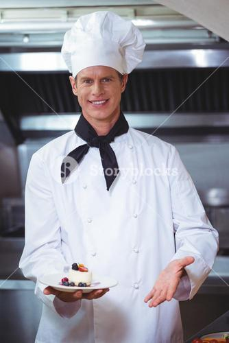 Proud chef holding a plate of cheesecake desert