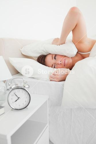 Good looking brunette woman awaking with a clock while lying