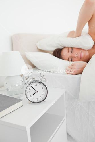 Cute brunette woman awaking with a clock while lying