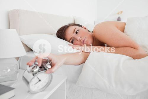 Gorgeous brunette female awaking with a clock while lying