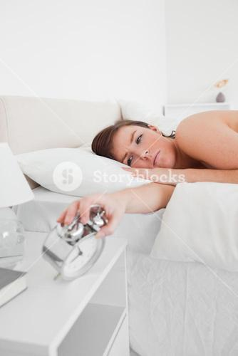 Attractive brunette female awaking with a clock while lying