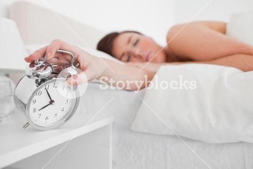 Charming brunette female awaking with a clock while lying