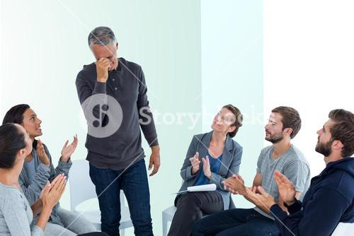 Composite image of rehab group applauding delighted man standing up