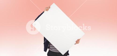 Composite image of man holding billboard in front of face