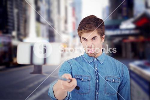 Composite image of hipster sticking out tongue while taking selfie