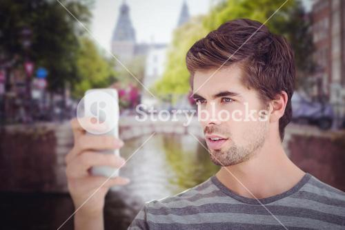 Composite image of man looking at mobile phonewhile standing
