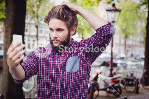 Composite image of confident hipster taking selfie