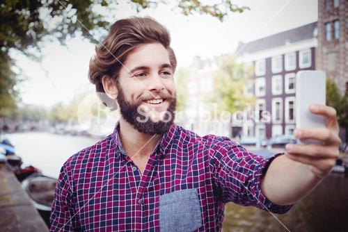Composite image of happy hipster taking selfie